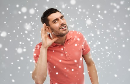 gesture, winter, christmas and people concept - man having hearing problem listening to something over snow on gray background Zdjęcie Seryjne