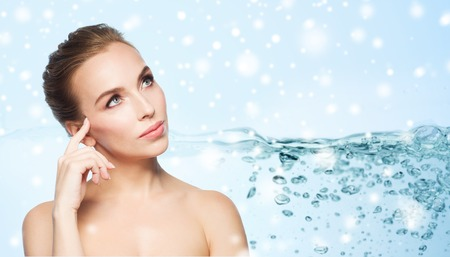 skin care, people, moisturizing and beauty concept - beautiful young woman face over water splash bubbles on blue background and snow