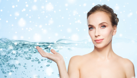 aqua naked: beauty, people, moisturizing, advertisement and skin care concept - smiling young woman holding something on palm of her hand over water splash bubbles on blue background and snow Stock Photo