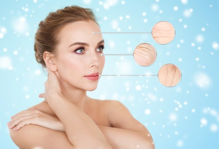 beauty, people, aging and skin care concept - beautiful young woman and circles with magnified facial wrinkles over blue background and snow