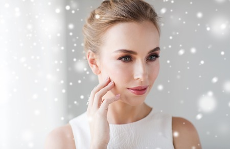white face: beauty, christmas, holidays and people concept - close up of beautiful smiling woman in white dress touching her face over snow Stock Photo