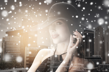 femme fatale: people, christmas, holidays, luxury and fashion concept - beautiful woman in black hat over dubai city with double exposure background and snow