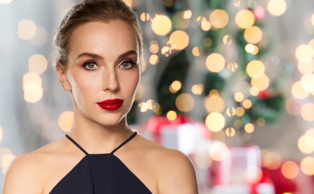 femme fatale: christmas, people, luxury and fashion concept - beautiful woman in black with red lips over holidays lights background