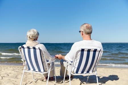 folding chair: family, old age, travel, tourism and people concept - happy senior couple sitting on deck chairs on summer beach