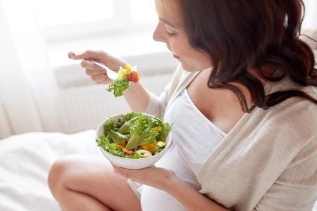 임신, 건강 식품 및 사람들이 개념 - 집에서 침대에서 아침 식사를 위해 야채 샐러드를 먹는 행복 한 임신 여자의 닫습니다