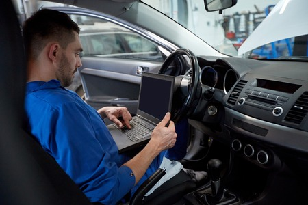 car service, repair, maintenance and people concept - mechanic man with laptop computer making system diagnostic at workshop 版權商用圖片 - 65551162