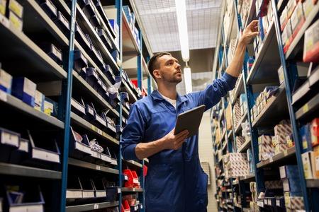 車のサービス、修理、保守および人々 のコンセプト - オート メカニック マニュアルまたはワーク ショップや倉庫でスペアを探してタブレット pc コ 写真素材