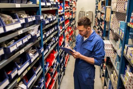 conceito de serviço, reparação, manutenção e pessoas de carro - auto mecânico homem ou smith escrevendo para área de transferência na oficina ou armazém Foto de archivo