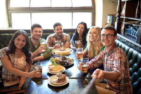 woman bar: people, leisure, friendship and technology concept - happy friends taking picture by selfie stick, drinking beer and eating snacks at bar or pub