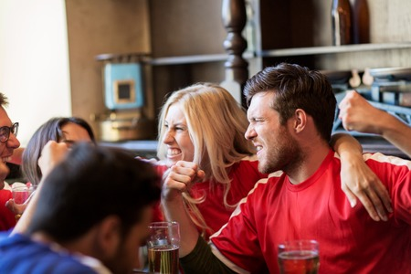 friends drinking: sport, people, leisure, friendship and entertainment concept - happy football fans or friends drinking beer and celebrating victory at bar or pub Stock Photo