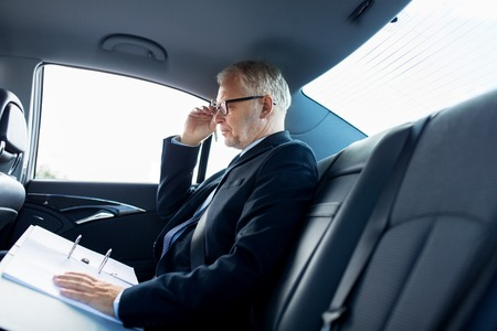 concepto de transporte, viaje de negocios, papeleo y personas - empresario senior con documentos de conducción en el asiento trasero del coche
