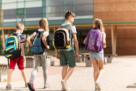niños saliendo de la escuela: la educación primaria, la amistad, la infancia y las personas concepto - grupo de estudiantes de la escuela primaria felices con mochilas caminando al aire libre de la parte posterior