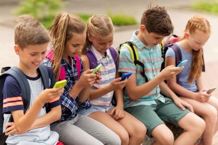 기본 교육, 우정, 어린 시절, 기술 및 사람들이 개념 - 행복 한 초등학교 학생 스마트 폰 및 배낭 야외 벤치에 앉아 그룹 스톡 콘텐츠 - 65551235
