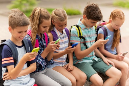 primary education, friendship, childhood, technology and people concept - group of happy elementary school students with smartphones and backpacks sitting on bench outdoors Stockfoto