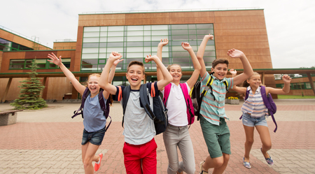 primary education, friendship, childhood and people concept - group of happy elementary school students with backpacks running and waving hands outdoors Reklamní fotografie - 65551239