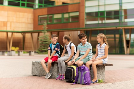 primary education, friendship, childhood, communication and people concept - group of happy elementary school students with backpacks sitting on bench and talking outdoors Imagens