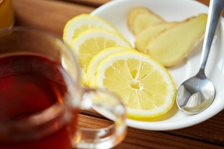 indigenous medicine: health, traditional medicine, folk remedy and ethnoscience concept - tea cup with lemon and ginger on plate with spoon Stock Photo