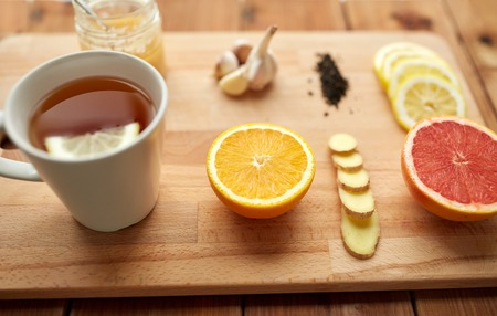 health, traditional medicine, folk remedy and ethnoscience concept - cup of ginger tea with honey, citrus and garlic on wooden background Stock Photo