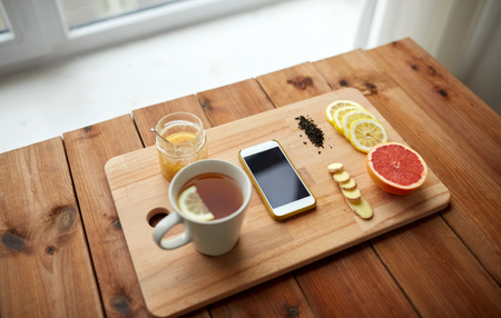 indigenous medicine: health, traditional medicine, folk remedy and ethnoscience concept - smartphone with cup of ginger tea, honey and citrus on wooden board