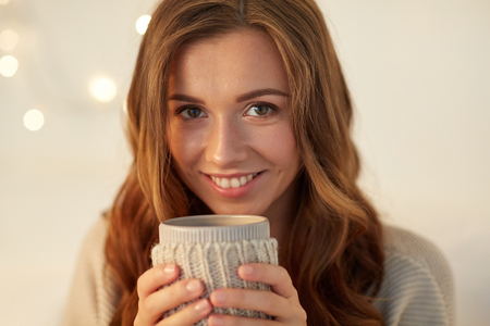 tea cosy: drink, christmas, winter, holidays and people concept - close up of happy young woman with cup of coffee or tea at home