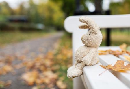 soledad: temporada, la infancia y el concepto de la soledad - conejo de juguete solitaria en banco en parque del otoño Foto de archivo
