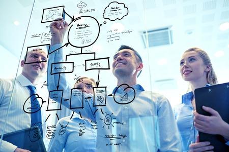 negocio, las personas, el trabajo en equipo y el concepto de planificación - sonriendo equipo de negocios con marcador y pegatinas trabaja en la oficina