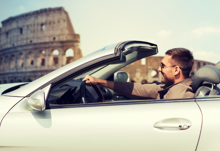 trip over: travel, tourism, road trip, transport and people concept - happy man driving cabriolet car over coliseum in rome background