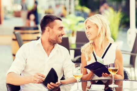 holiday spending: date, people, payment and financial independence concept - happy couple with cash money in wallets and wine glasses paying bill at restaurant