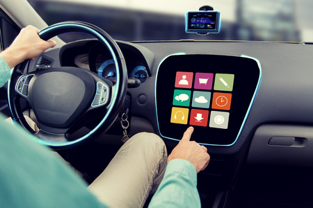 onboard: transport, road trip, car driving, technology and people concept - close up of male hand pointing to on-board computer menu