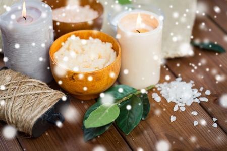 natural therapy: beauty, spa, therapy and natural cosmetics concept - body scrub, salt and candles on wood over snow