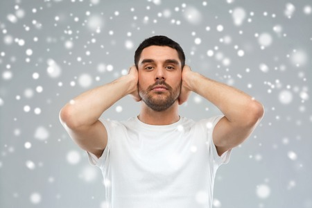 stress, hearing problem, winter, christmas and people concept - latin man covering his ears with hand palms over snow on gray background