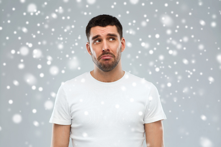 unhappy man: emotion, sadness, winter, christmas and people concept - unhappy young man over snow on gray background