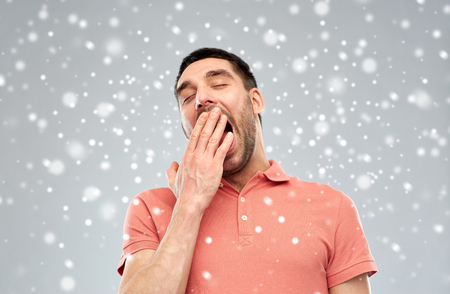 cansancio: tiredness, bedtime, winter, christmas and people concept - tired yawning man over snow on snow background
