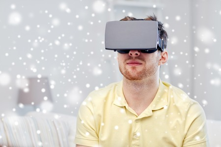 entertainment concept: technology, gaming, augmented reality, entertainment and people concept - young man with virtual headset or 3d glasses playing video game over snow Stock Photo