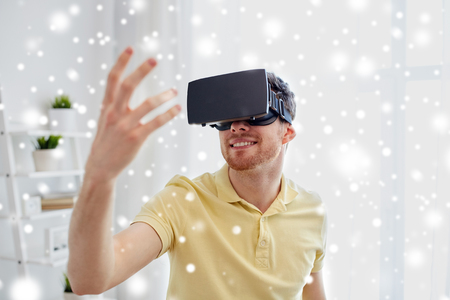 entertainment concept: technology, augmented reality, gaming, entertainment and people concept - happy young man with virtual headset or 3d glasses playing video game over snow