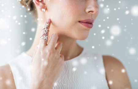 jewel: christmas, holidays, beauty, jewelry and luxury concept - close up of beautiful woman with golden ring and diamond earring over snow