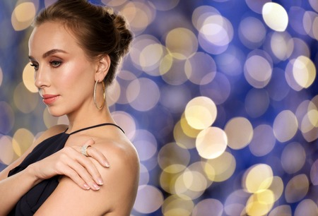 diamond ring: people, luxury, jewelry and fashion concept - beautiful woman in black wearing diamond earring and ring over blue holidays lights background Stock Photo
