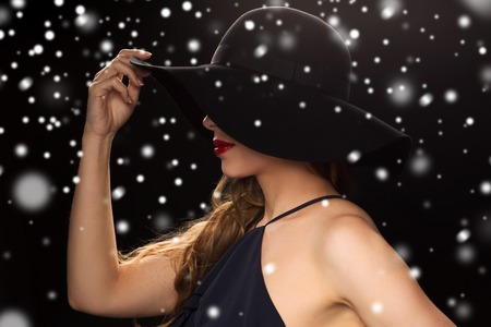 black hat: people, christmas, holidays, luxury and fashion concept - beautiful woman in hat over black background and snow