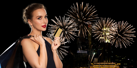 young woman smiling: people, holidays, new year, luxury and sale concept - beautiful woman with credit card and shopping bags over night city firework lights background