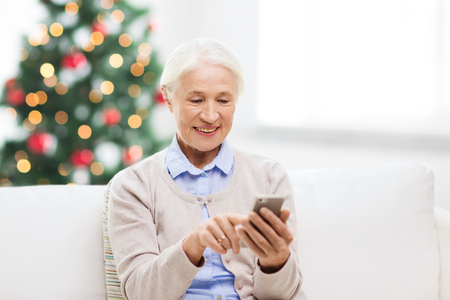 indoor background: technology, communication, holidays age and people concept - happy senior woman with smartphone texting message at home over christmas tree lights background