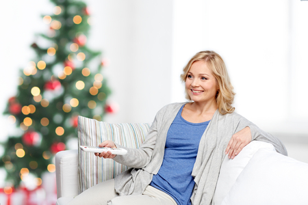 television, holidays, leisure and people concept - smiling woman sitting on couch with tv remote control at home over christmas tree lights background