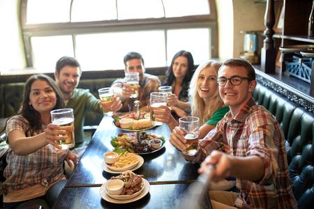 la gente, el ocio, la amistad y el concepto de la tecnología - amigos felices que toman el cuadro por el palo de autofoto, beber cerveza y comer bocadillos en el bar o pub