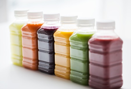healthy eating, drinks, diet and detox concept - close up of plastic bottles with different fruit or vegetable juices on white