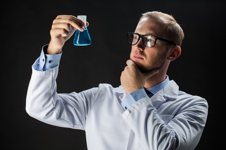 science, chemistry, research and people concept - young scientist holding test flask with chemical over black background Stock Photo