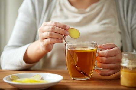 la salud, la medicina tradicional y la etnociencia concepto - cerca de la mujer adición de jengibre para la taza de té con limón y miel Foto de archivo