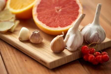 traditional medicine, cooking and ethnoscience concept - orange, grapefruit with ginger and garlic on wooden board