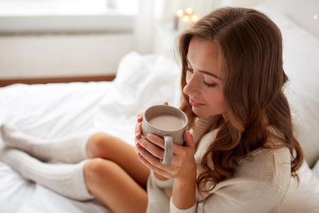 morning, leisure, christmas, winter and people concept - happy young woman with cup of coffee or cocoa in bed at home Zdjęcie Seryjne - 65553007