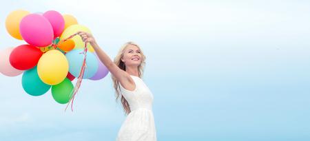 zomervakantie, feest en lifestyle concept - mooie vrouw met kleurrijke ballonnen buiten Stockfoto