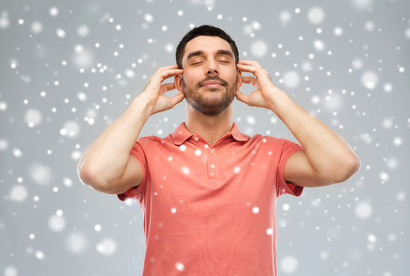 music, gesture, winter, christmas and people concept - happy smiling man listening to music with imaginary headphones over snow on gray background