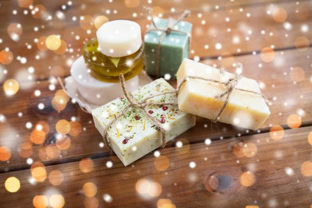 beauty, spa, bodycare, bath and natural cosmetics concept - handmade soap bars on wood over lights and snow